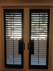 open shutters covering french doors with cutouts for the door handles