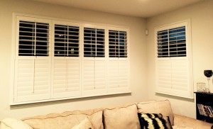 shutters covering two windows in a living room
