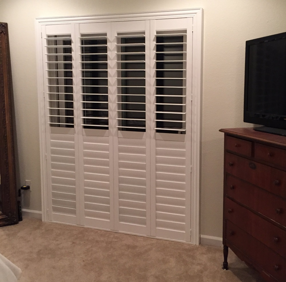 large 4 panel shutters convering sliding glass goor in bedroom