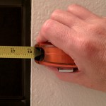 person measurng window opening with tape measure