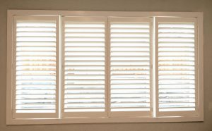4 panel plantation shutters installed on wide window