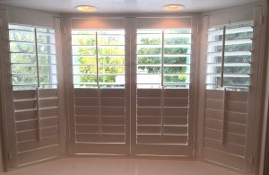 plantation shutters provide privacy for bay windows